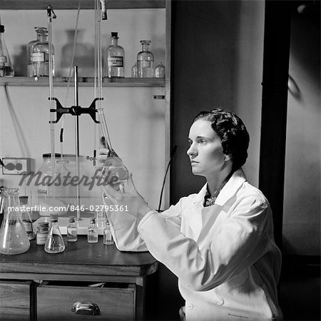 1930s 1940s WOMAN SCIENTIST IN LAB COAT HOLDING UP AND EXAMINING BEAKER OF LIQUID Stock Photo - Rights-Managed, Image code: 846-02795361