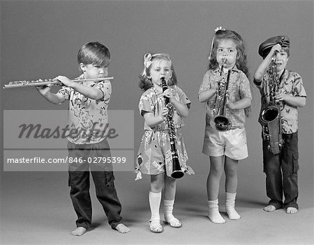 TWO BOYS AND TWO GIRLS PLAYING FLUTE CLARINET TRUMPET AND SAXOPHONE INDOOR Stock Photo - Rights-Managed, Image code: 846-02795399
