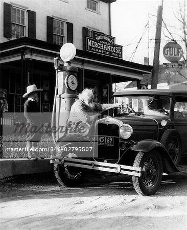 ELDERLY GRANDFATHER FILLING UP FORD CAR IN FRONT OF PENNSYLVANIA GENERAL STORE WITH GRANDSON WATCHING 1930s Stock Photo - Rights-Managed, Image code: 846-02795507