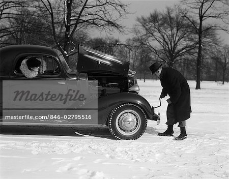 1930s 1940s WOMAN PASSENGER WATCHING MAN MOTORIST TRY TO CRANK START A CHEVROLET COUPE STALLED IN SNOW Stock Photo - Rights-Managed, Image code: 846-02795516