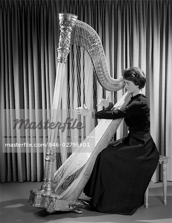 1960s WOMAN MUSICIAN IN FORMAL DRESS PERFORMING PLAYING HARP ON STAGE Stock Photo - Rights-Managed, Image code: 846-02795601
