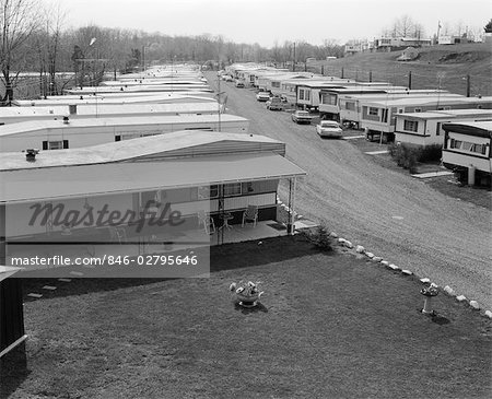 1970s TRAILER PARK WITH ROWS OF MOBILE HOMES ON EITHER SIDE OF GRAVEL ROAD Stock Photo - Rights-Managed, Image code: 846-02795646