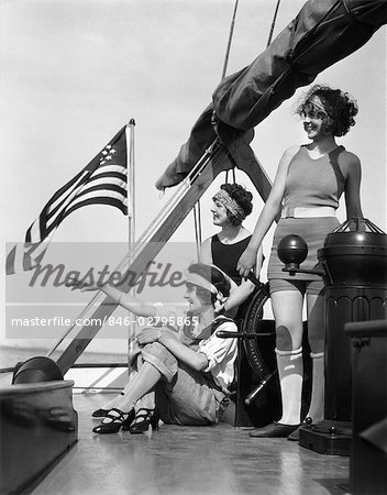 1920s GROUP OF THREE WOMEN UPON DECK OF SAILBOAT POINTING TO LEFT ...