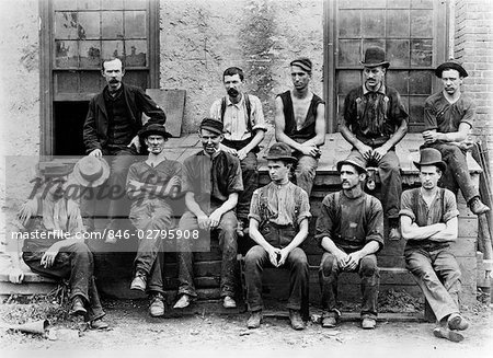 1890s 1900s GROUP OF 11 FACTORY WORKERS SEATED OUTSIDE OF BUILDING