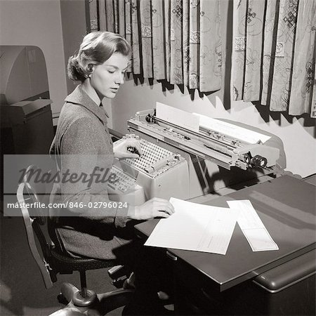 1950s SECRETARY SITTING AT DESK READING FROM LEDGER MAKING ENTRIES ON COMPTOMETER Stock Photo - Rights-Managed, Image code: 846-02796024