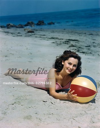 1940s 1950s BRUNETTE WOMAN LYING ON BEACH HOLDING BEACH BALL Stock Photo - Rights-Managed, Image code: 846-02796102