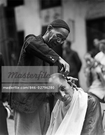 1920s 1930s CHINESE MAN SIDEWALK BARBER IN SKULL SHAVING ANOTHER MAN'S HEAD HONG KONG CHINA Stock Photo - Rights-Managed, Image code: 846-02796280