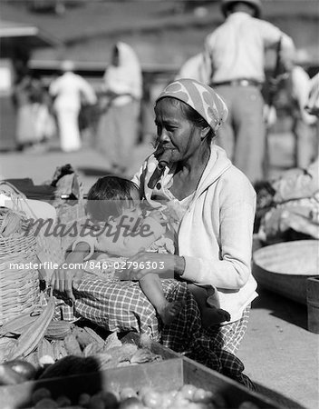 1920s 1930s MOTHER SITTING HOLDING BABY CHILD IN MARKET PLACE WOMAN SMOKING CIGAR CHEROOT BAGUIO PHILIPPINES Stock Photo - Rights-Managed, Image code: 846-02796303