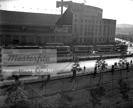1940s EXTERIOR OF YANKEE STADIUM WITH A COCA COLA BANNER ON WALL TREE LINED STREET WITH PEDESTRIANS NYC USA Stock Photo - Rights-Managed, Image code: 846-02796357