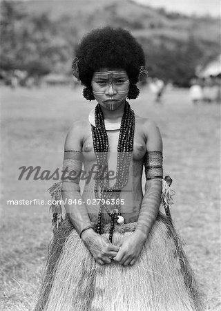 1920s 1930s NATIVE WOMAN TOPLESS NATIVE COSTUME GRASS SKIRT TATTOOS NECKLACE HANUABADA VILLAGE PORT MORESBY NEW GUINEA Stock Photo - Rights-Managed, Image code: 846-02796385
