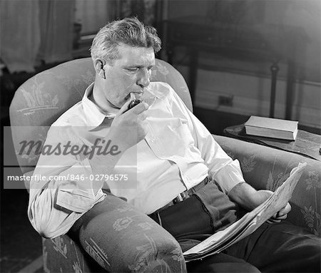 1930s MAN SITTING CHAIR READING NEWSPAPER SMOKING PIPE Stock Photo - Rights-Managed, Image code: 846-02796575