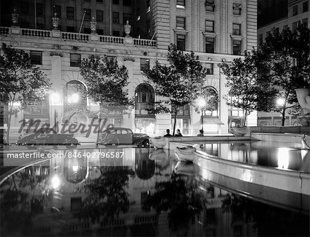 1930s NIGHT SCENE 5TH AVENUE HOTEL FRONT TREE LINED SIDEWALK MOTORCARS POOL AND PEDESTRIANS STREET LAMPS REFLECTING ON SURFACES Stock Photo - Rights-Managed, Image code: 846-02796587