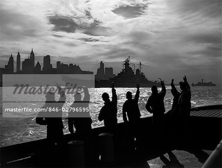 1950s SILHOUETTED SAILORS DECK OF SHIP WAVING SALUTE TO PASSING USN BATTLESHIP AT NIGHT AGAINST NEW YORK CITY SKYLINE Stock Photo - Rights-Managed, Image code: 846-02796595