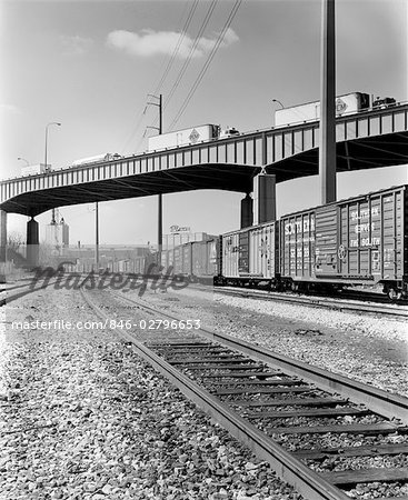 1970s ANGLED VIEW OF FREIGHT TRAIN PASSING UNDER HIGHWAY BRIDGE