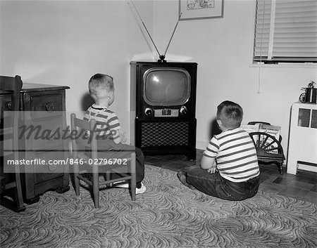 1950s TWO BOYS SITTING IN LIVING ROOM WATCHING TELEVISION