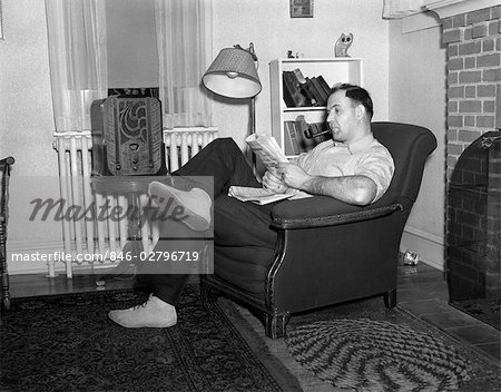 1950s MAN SITTING IN CHAIR IN LIVING ROOM SMOKING PIPE READING PAPER LISTENING TO RADIO Stock Photo - Rights-Managed, Image code: 846-02796719