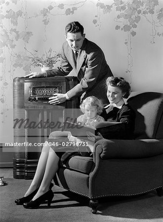 1930s 1940s FAMILY LISTENING TO RADIO WHILE MOTHER READS BOOK TO LITTLE GIRL SEATED IN HER LAP IN ARMCHAIR Stock Photo - Rights-Managed, Image code: 846-02796731