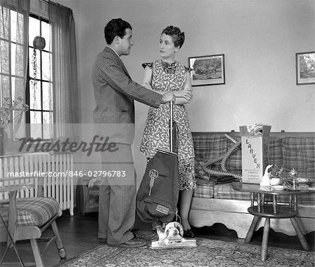 1930s 1940s SALESMAN IN SUIT DEMONSTRATING VACUUM CLEANER BY A WINDOW IN A LIVING ROOM TO A LADY WEARING A PRINT DRESS Stock Photo - Rights-Managed, Image code: 846-02796783