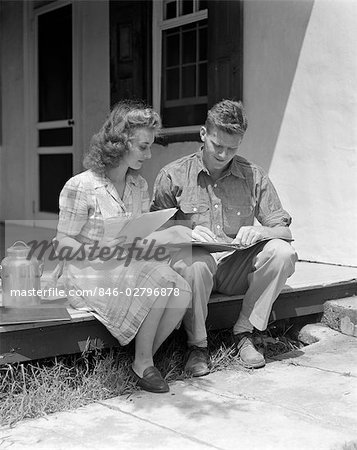 1940s COUPLE MAN WOMAN SITTING ON PORCH FARM HOUSE REVIEWING LEDGER PAPERS MILK METAL CONTAINER BY WOMAN Stock Photo - Rights-Managed, Image code: 846-02796878