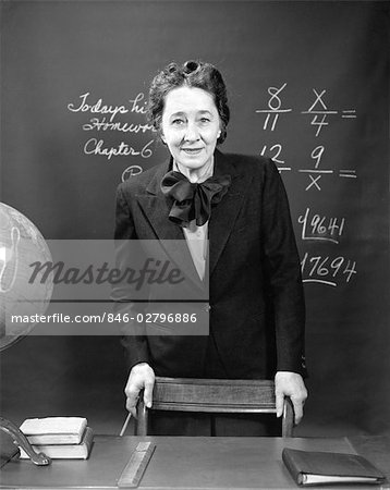 1940s SMILING SCHOOL TEACHER STANDING BEHIND HER DESK & IN FRONT OF THE BLACK BOARD WITH FRACTIONS Stock Photo - Rights-Managed, Image code: 846-02796886
