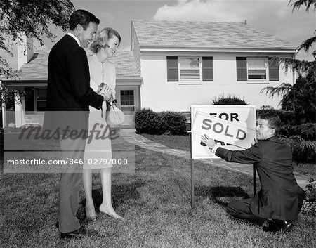 1960s SMILING COUPLE STANDING ON FRONT LAWN OF NEW HOUSE LOOKING DOWN AT REALTOR PUTTING UP SOLD SIGN Stock Photo - Rights-Managed, Image code: 846-02797000