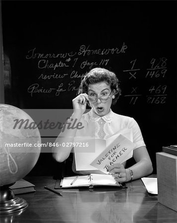1950s SCHOOL TEACHER AT DESK HAND TO GLASSES EXPRESSION OF SURPRISE OPENING A VALENTINE FOR TEACHER GLOBE BLACKBOARD Stock Photo - Rights-Managed, Image code: 846-02797216