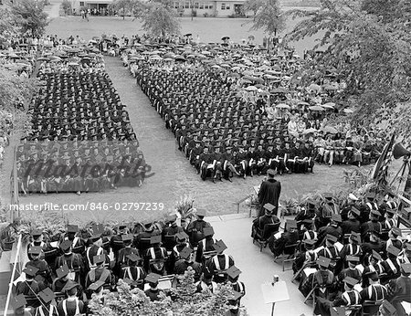 1960s VIEW FROM ABOVE STAGE AREA LOOKING DOWN ONTO 2 SECTIONS OF SEATED GRADUATES WITH SURROUNDING AUDIENCE HOLDING UMBRELLAS