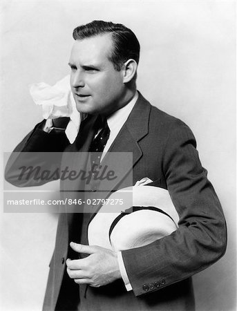 1930s MAN IN SUIT HOLDING HAT WIPING FACE WITH HANDKERCHIEF Stock Photo - Rights-Managed, Image code: 846-02797275