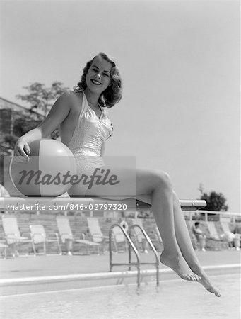 1950s BATHING BEAUTY IN SATIN ONE-PIECE SITTING WITH LEGS HANGING OFF DIVING BOARD HOLDING BEACH BALL Stock Photo - Rights-Managed, Image code: 846-02797320