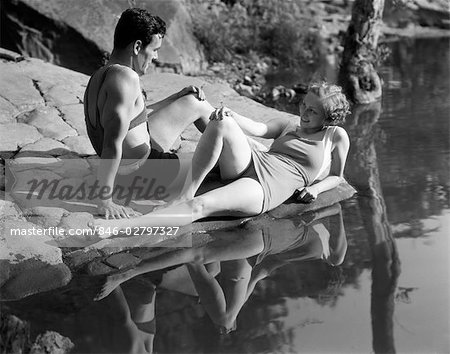 1930s COUPLE LYING ON ROCKS NEAR WATER WEARING BATHING SUITS Stock Photo - Rights-Managed, Image code: 846-02797327