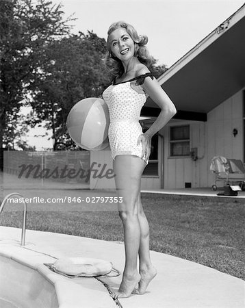 1950s WOMAN HOLDING BEACH BALL STANDING BY IN GROUND SWIMMING POOL WEARING BATHING SUIT Stock Photo - Rights-Managed, Image code: 846-02797353