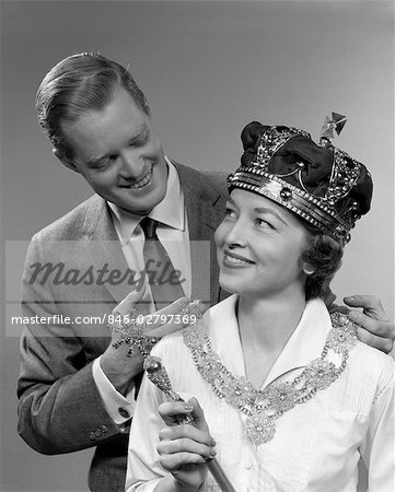 1950s MAN HOLDING NECKLACE ON WOMAN WEARING CROWN AND HOLDING SCEPTER