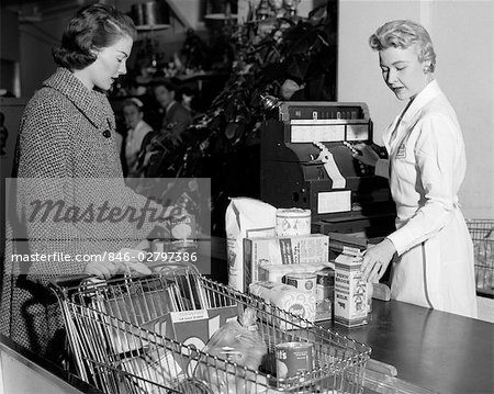 1950s WOMAN AT GROCERY STORE CHECKOUT COUNTER HANDING ITEMS OVER FOR CASHIER TO RING UP ON CASH REGISTER Stock Photo - Rights-Managed, Image code: 846-02797386