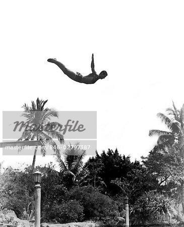 1930s MAN POISED MIDAIR ARMS OUT JUMPING FROM DIVING BOARD INTO POOL Stock Photo - Rights-Managed, Image code: 846-02797387