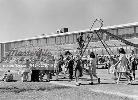 1950s ELEMENTARY SCHOOL PLAYGROUND AT RECESS WITH CHILDREN PLAYING ON SLIDE & SWING SET