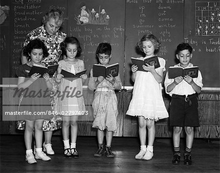 1930s LINE-UP OF 5 ELEMENTARY SCHOOL STUDENTS IN FRONT OF BLACKBOARD READING BOOKS WITH TEACHER LOOKING ON Stock Photo - Rights-Managed, Image code: 846-02797403