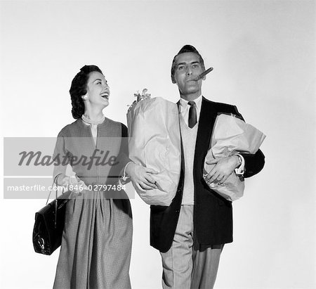 1950s COUPLE WALKING WOMAN SMILING AT MAN CARRYING GROCERY BAGS SMOKING CIGAR Stock Photo - Rights-Managed, Image code: 846-02797484