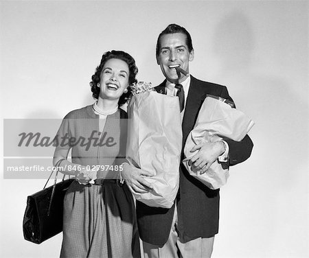 1950s COUPLE SMILING WOMAN MAN CARRYING GROCERY BAGS SMOKING CIGAR SEAMLESS Stock Photo - Rights-Managed, Image code: 846-02797485