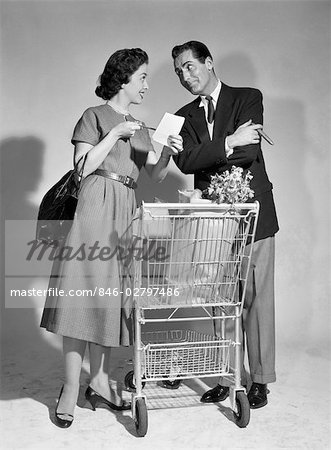 1950s COUPLE MAN WOMAN SHOPPING CART REVIEWING GROCERY LIST MAN HAS CIGAR IN HAND Stock Photo - Rights-Managed, Image code: 846-02797486