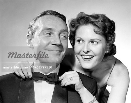1950s COUPLE DRESSED IN FORMAL ATTIRE WOMAN PULLING ON MAN'S BOWTIE