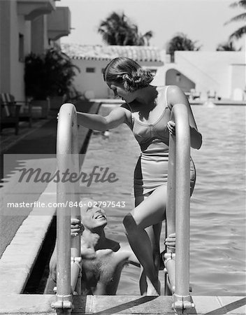 1930s COUPLE WOMAN WEARING ONE PIECE BATHING SUIT CLIMBING LADDER OUT OF SWIMMING POOL LOOKING DOWN AT MAN SMILING MIAMI BEACH FLORIDA