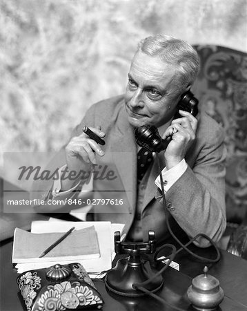 1930s ELDER MAN SITTING AT DESK SMOKING CIGAR TALKING ON TELEPHONE Stock Photo - Rights-Managed, Image code: 846-02797616