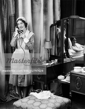 1920s 1930s MAID IN UNIFORM TALKS ON TELEPHONE IN FRONT OF VANITY DRESSING TABLE OTHER WOMAN IS SEEN AS REFLECTION IN MIRROR Stock Photo - Rights-Managed, Image code: 846-02797628