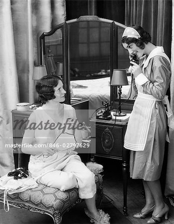 1920s 1930s WOMAN IN LINGERIE IN FRONT OF MIRRORED VANITY BUREAU LOOKS AT MAID IN UNIFORM ANSWERING THE TELEPHONE BEDROOM Stock Photo - Rights-Managed, Image code: 846-02797629