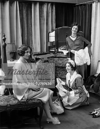 1920s 1930s THREE WOMEN IN BEDROOM ONE IN LINGERIE TALKING TELEPHONE LOOKING MAID PACKING SUITCASES TRUNK MIRROR VANITY TRAVEL Stock Photo - Rights-Managed, Image code: 846-02797630