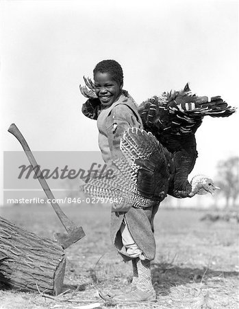 1920s 1930s AFRICAN AMERICAN BOY IN KNICKERS HOLDING A LIVE TURKEY OVER HIS SHOULDER STANDING BY A LOG EMBEDDED WITH AN AX Stock Photo - Rights-Managed, Image code: 846-02797647