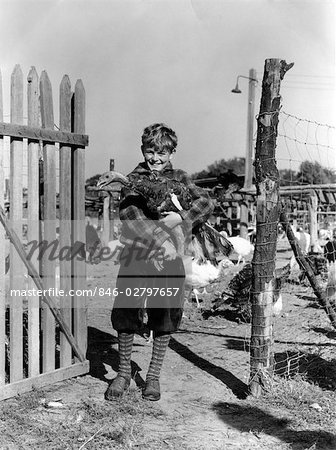1920s 1930s SMILING YOUNG BOY KNICKERS HOLDING TURKEY BY FENCE ON TURKEY FARM Stock Photo - Rights-Managed, Image code: 846-02797657