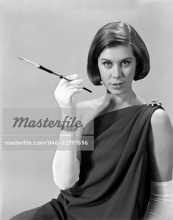 1960s FORMALLY ELEGANTLY DRESSED YOUNG WOMAN SEXY EXPRESSION HOLDING LONG CIGARETTE HOLDER WEARING LONG WHITE GLOVES Stock Photo - Rights-Managed, Image code: 846-02797696