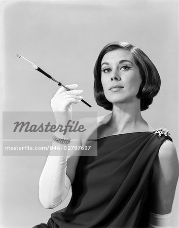 1960s FORMALLY ELEGANTLY DRESSED YOUNG WOMAN ARROGANT EXPRESSION HOLDING LONG CIGARETTE HOLDER WEARING LONG WHITE GLOVES Stock Photo - Rights-Managed, Image code: 846-02797697