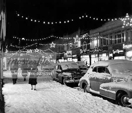 1940s 1950s WINTER CITY STREET SCENE WITH PEDESTRIANS IN SNOW CHRISTMAS LIGHTS Stock Photo - Rights-Managed, Image code: 846-02797719